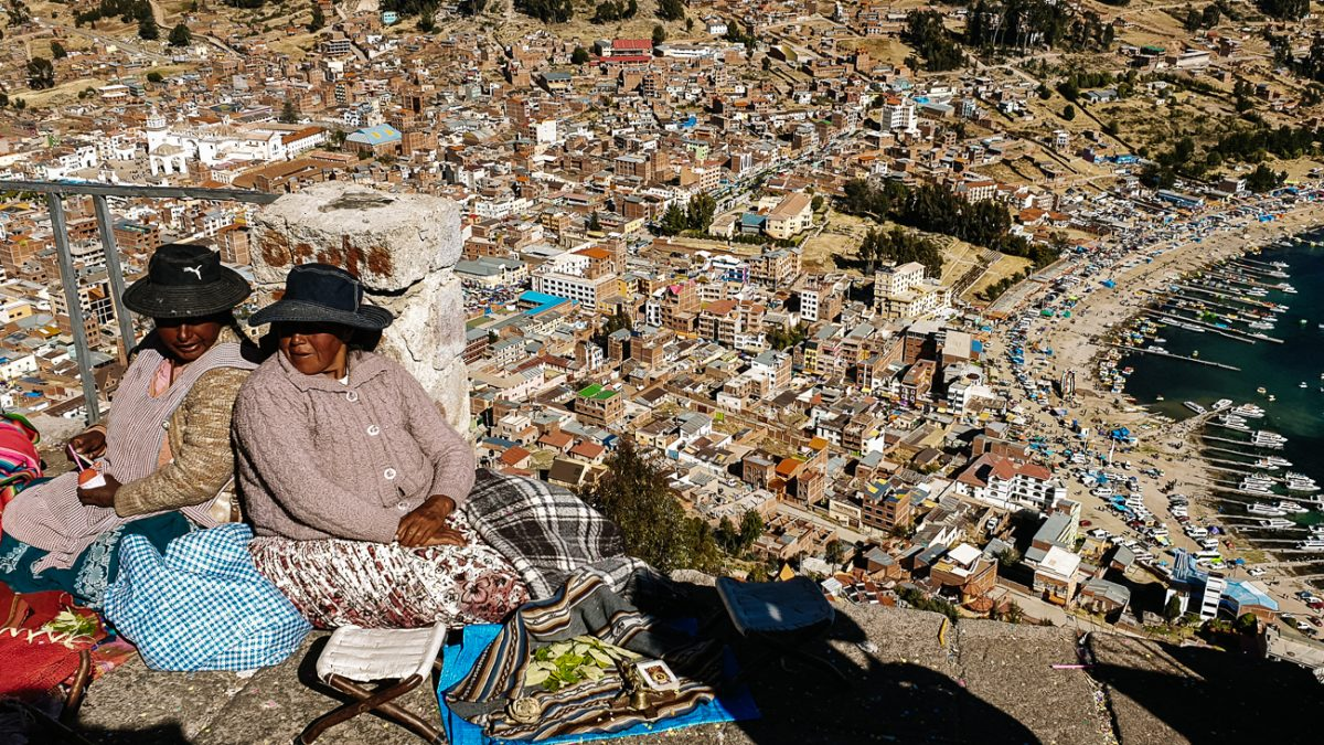 women sitting on Cerro Calvario during Independence Day, one of the best things to do in Copacabana Bolivia