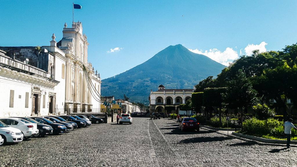 plaza central in antigua guatemala with volcano view