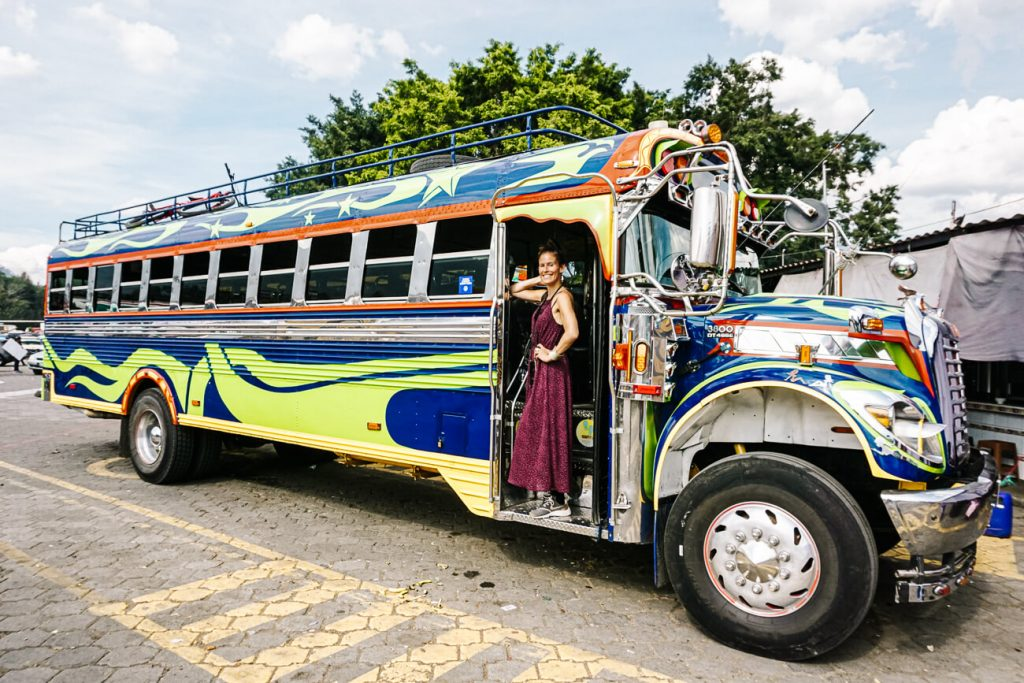 woman in front of colorful bus | Things to do in Guatemala travel tips