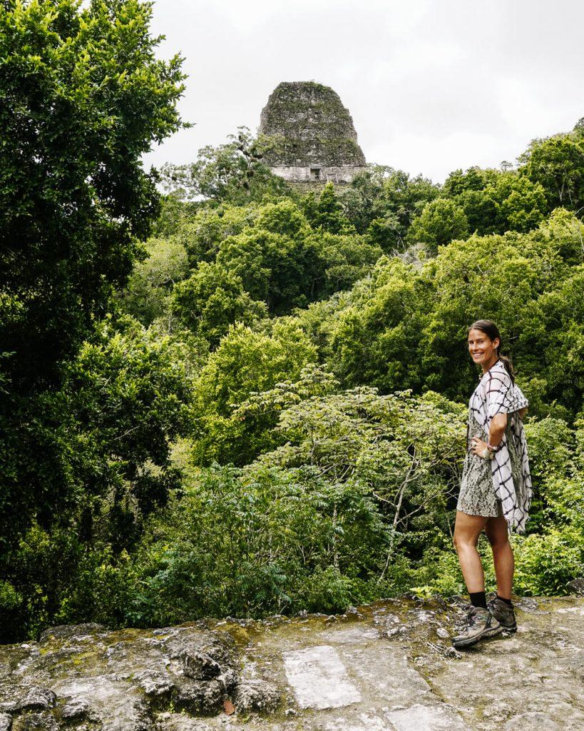 vrouw voor piramide in Tikal in Guatemala